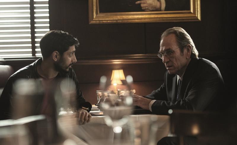 Riz ahmed (Aaron Kalloor) et Tommy Lee Jones (Robert Dewey) discutent sérieusement assis à table.