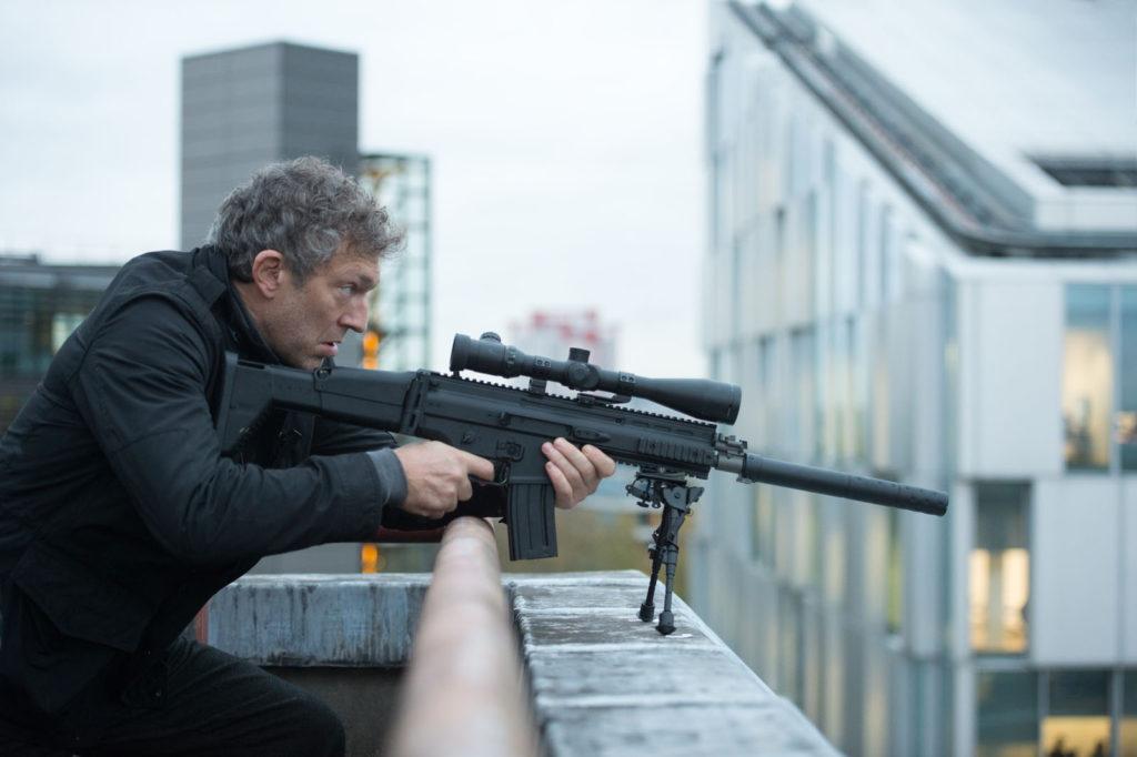 Vincent Cassel (Asset) est sur un toit et vise au sniper.